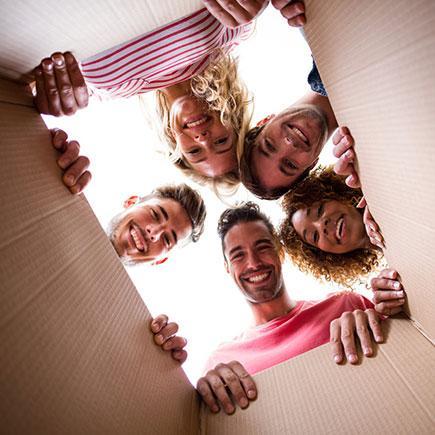 Gruppe von Menschen die in einen Karton schauen