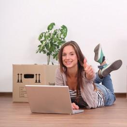 Single Frau mit Laptop in leerer Wohnung